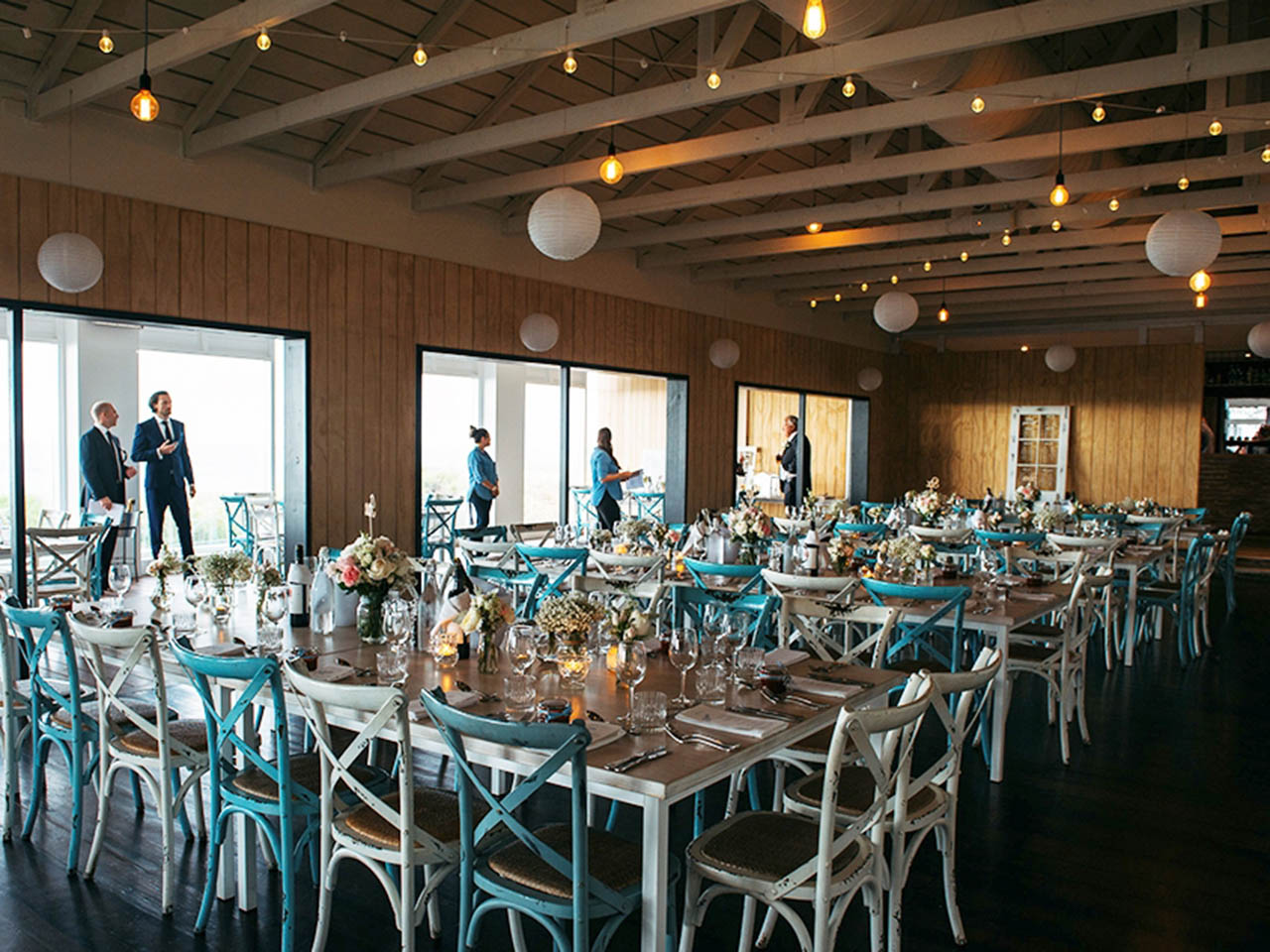 Tables Set Up For A Wedding With Lights And Lanterns at Coast Port Beach Oceanside Venue
