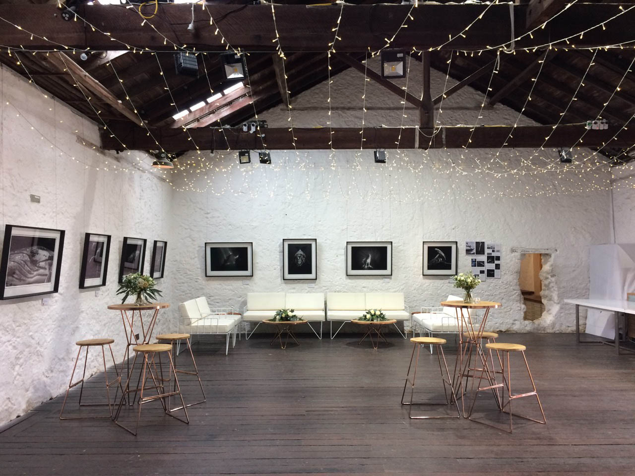 A Gallery Set Up With A Couch And Artwork