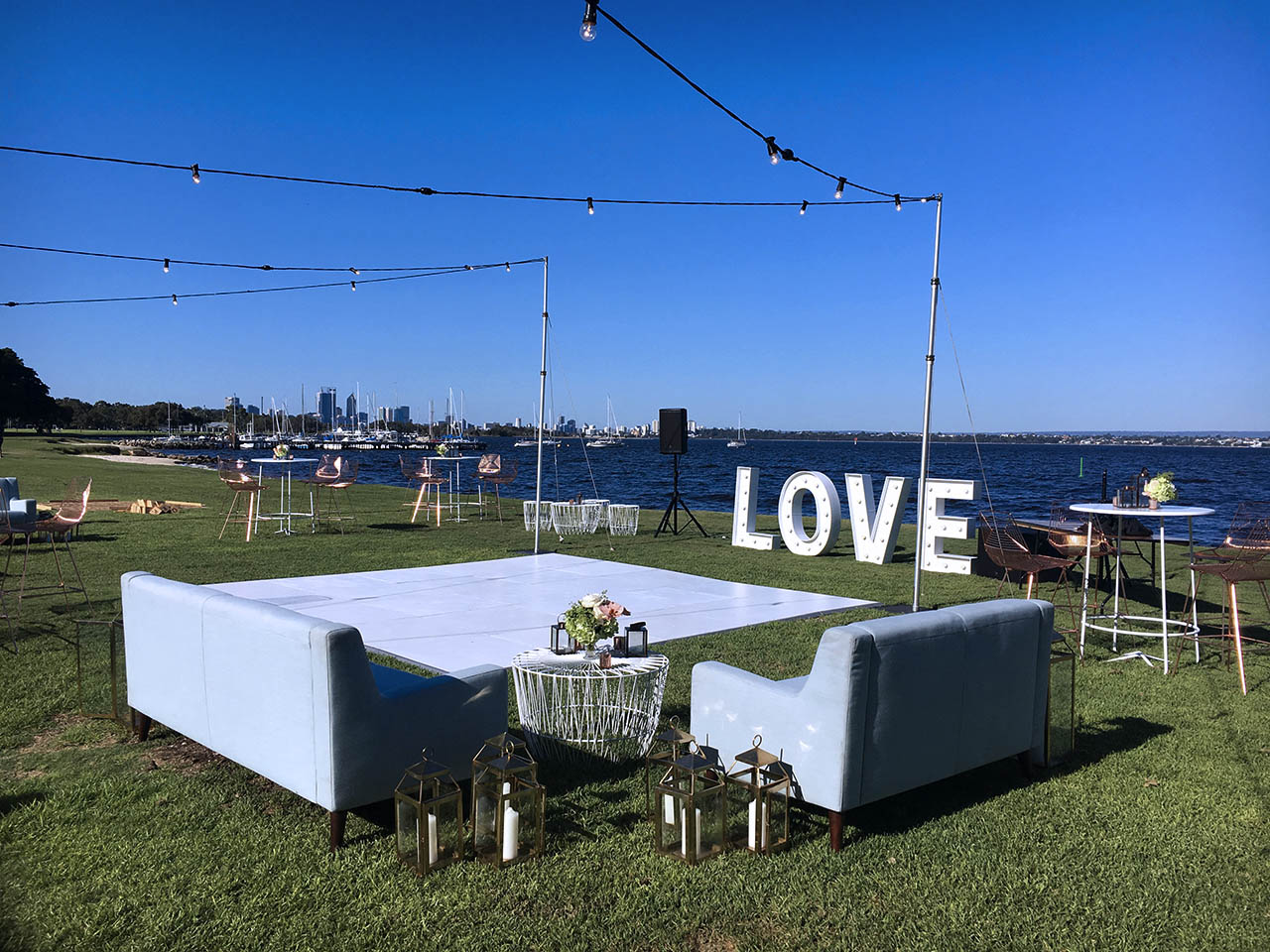 Gorgeous Daytime Riverside Setting With Couches And A Large Light-up Sculpture Of The Words