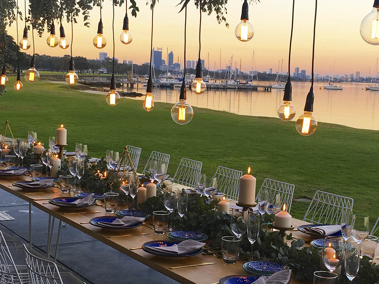 Beautiful Outdoor River-side Wedding Dining Room Setting With Long-table And Large Hanging Light Bulbs. Table Is Decorated With Vines, Wine Classes, Roses, Lit Candles And Dining Set.