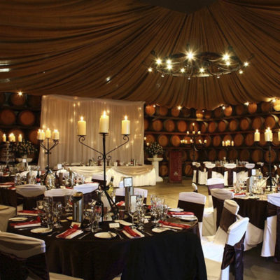White Round Tables With Candles And Rusty Walls.