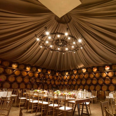 oak barrel filled room with dining tables, drapes and chandelier