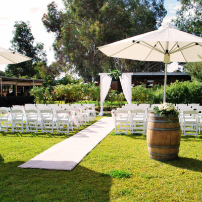Outdoor wedding scene with white chairs on lawn