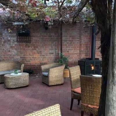 Tables And Chairs With Couch, Brick Walls, Ceiling With Tree Twigs And A Tree