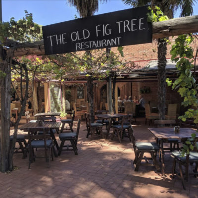Entrance to Old Fig Tree with wooden sign in foreground and tables and chairs in the courtyard