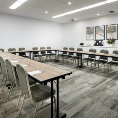 Conference room tables and chairs set up in a U shape ready for a presentation or meeting