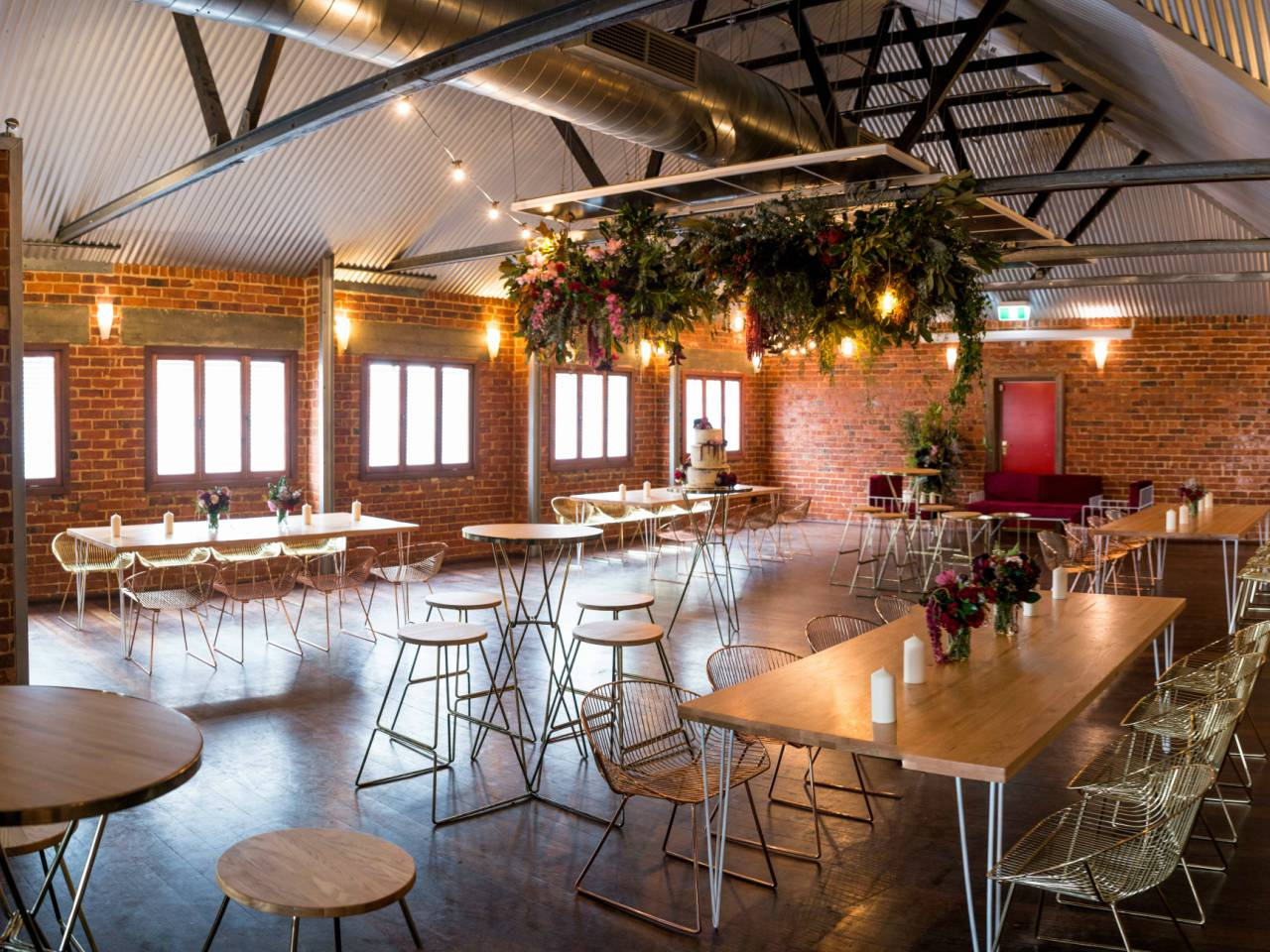A Beautiful Wooden And Brick Room With Lights And Tables.