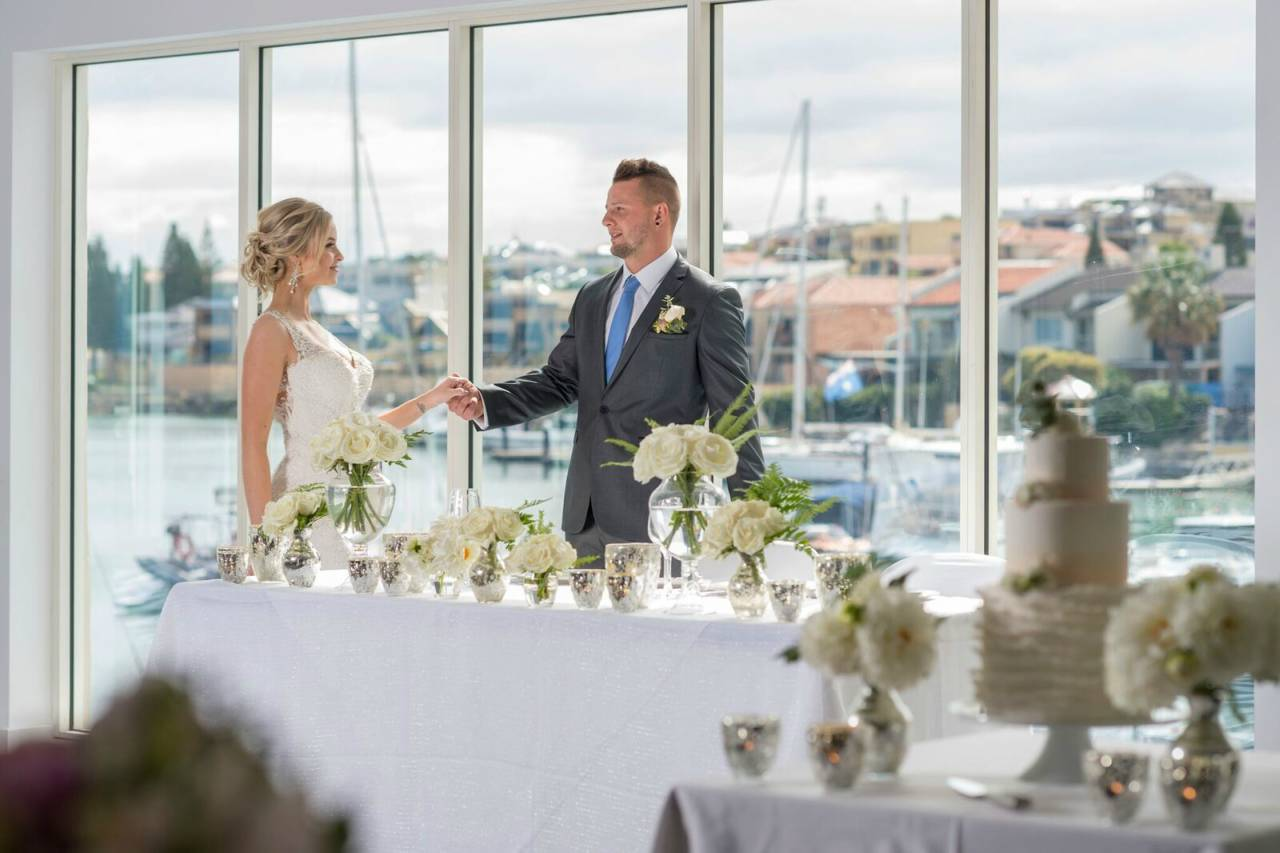 A Bride And Groom Holding Hands Surrounded By Flowers With A Open View Of The Marina.