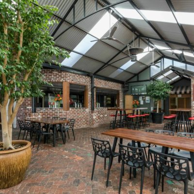 A Beautiful Undercover Brick Pub With Trees And Picnic Benches.