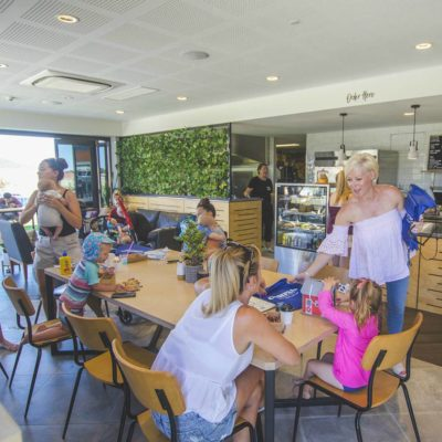 Mother And Children Meeting Inside The Cafe.