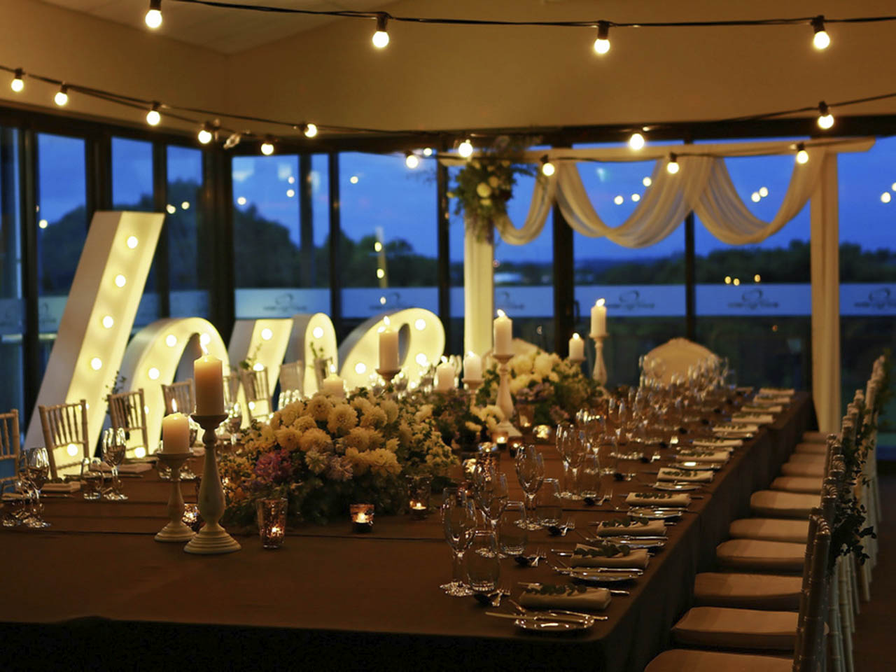 A Beautiful Table Set Out With Lights On The Celling And A Love Sign.