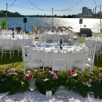 Gorgeous daytime riverside dining setting with white tables overlooking the Swan River and Perth City in the background. The worded sculpture