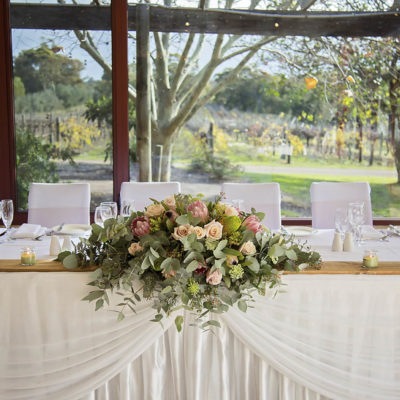 Wedding top table setting with bouquet of flowers, white seats and table decorations overlooking winery