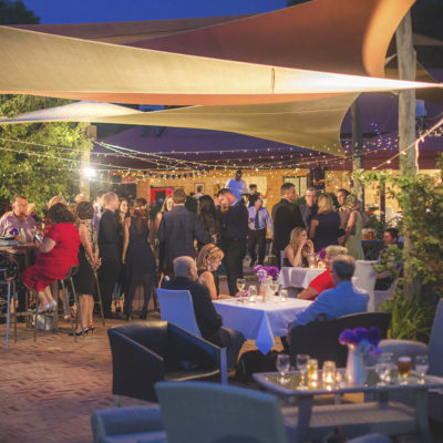 Outdoor wedding crowd standing and sitting chatting under canvas canopy and string lights