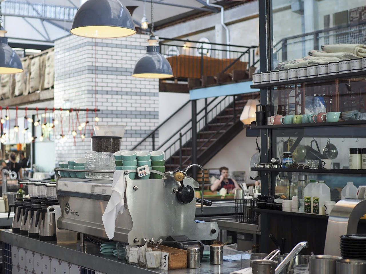Cafetiere with green cups under large lamps with mezzanine stairway backdrop leading to mezzanine level