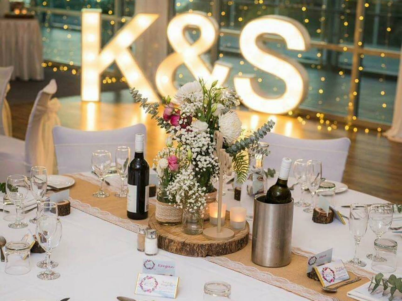 A Wine And Flower Display With Fairylights Behind.