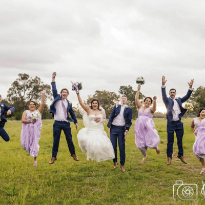 A fun photo of the bride in the centre, bridesmaids dressed in pink and bride grooms dressed in suits jumping for joy in a vineyard