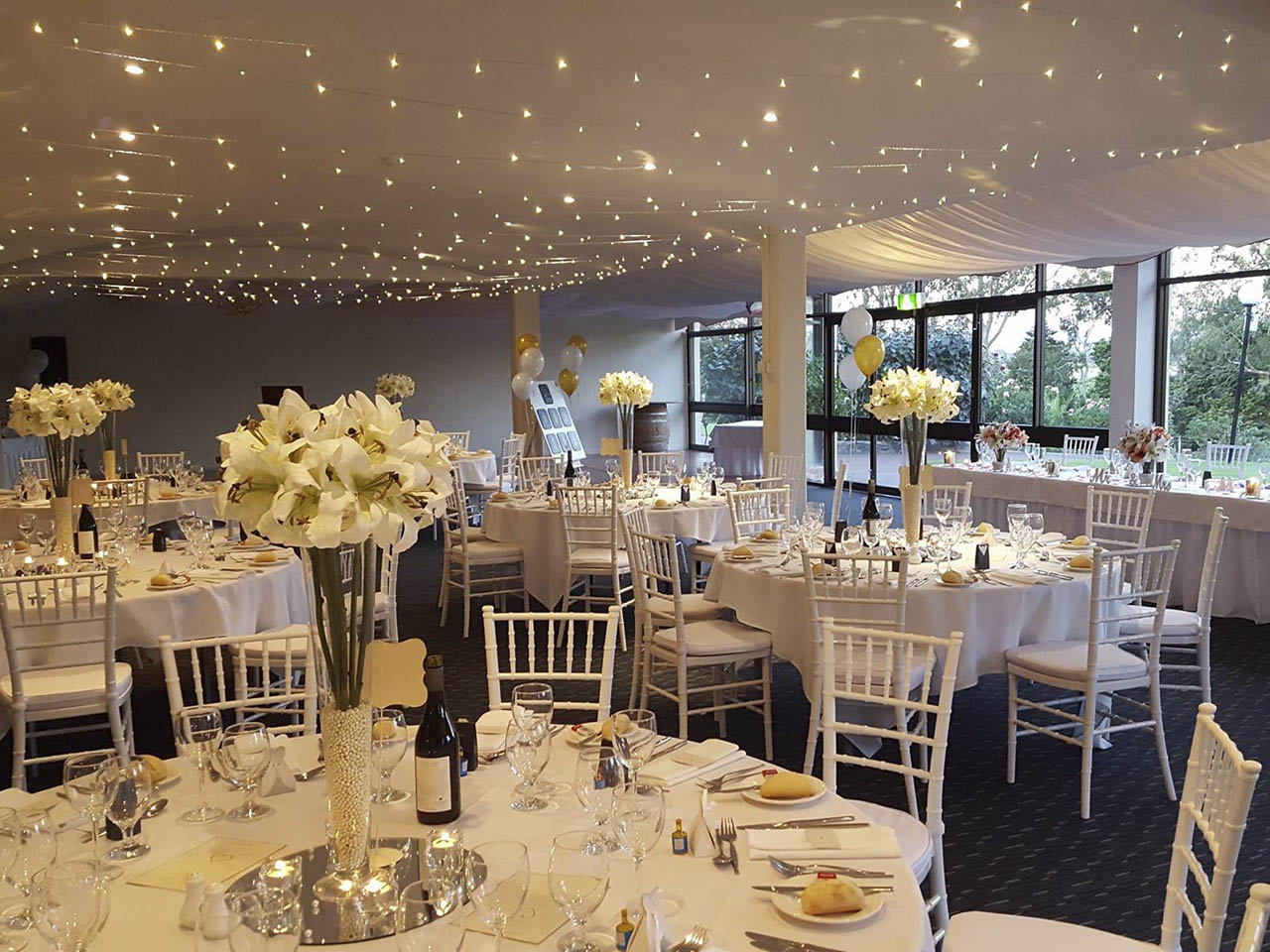 Beautiful wedding dining room setting with white tables, white lilies, balloons in the background and spotlights on ceiling overlooking greenery