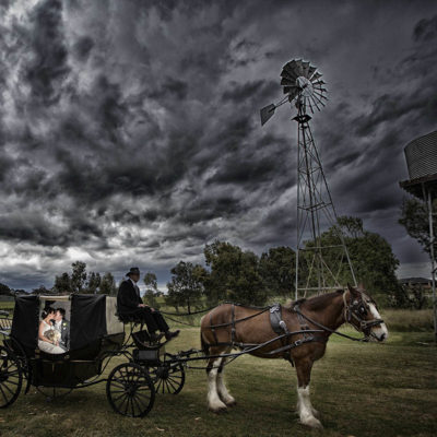 A stunning mood setting of a wedding couple in a horse and carriage under dark cloudy skies, windmill and water tank in a field
