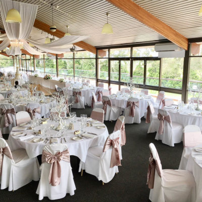 Beautiful wedding dining room setting with white tables, pink ribbons wrapped around chairs and sloping ceiling overlooking winery