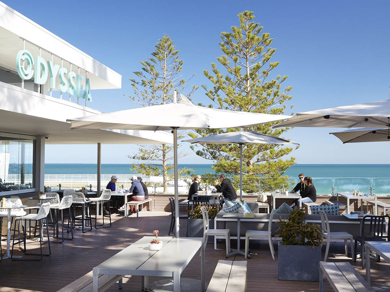 Odyssea's Terrace With Tables, Chairs, Umbrella Few Guests And Sea View