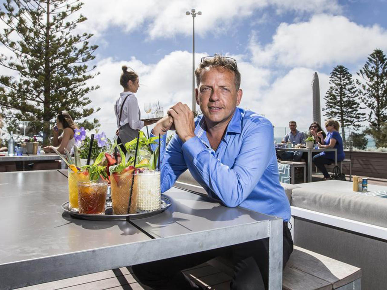 Man With Variety Of Fresh Juice Sitting In Odeyssea's Open Air Restaurant