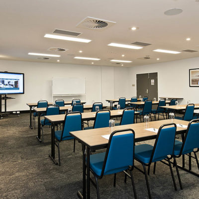 An empty conference room with desks and chairs set up for a conference