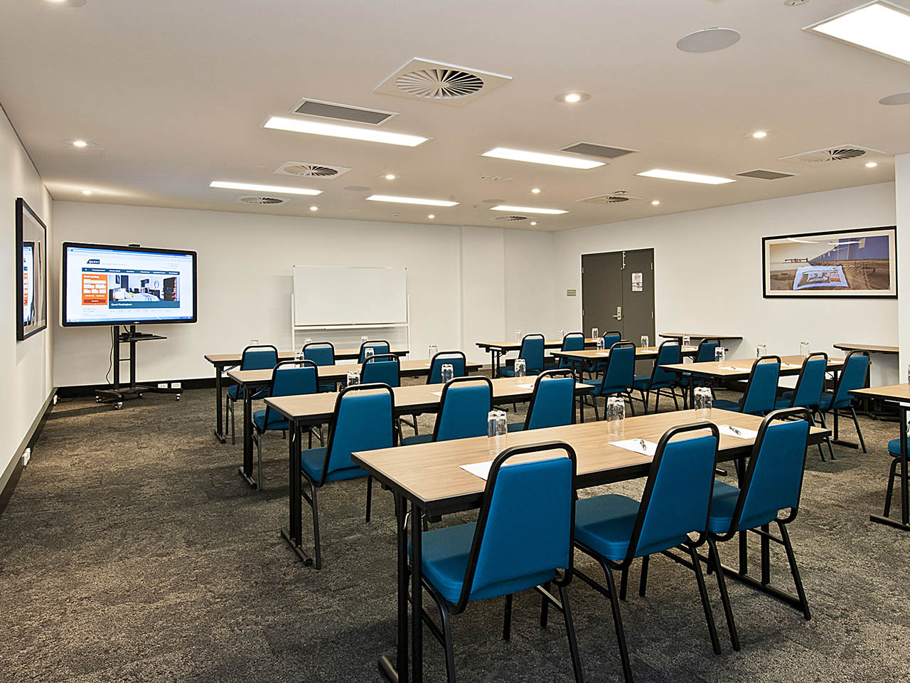 An Empty Conference Room With Desks And Chairs Set Up For A Conference.