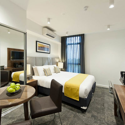 A Beautiful Hotel Bedroom With Flat Screen TV And Fruit Bowl.