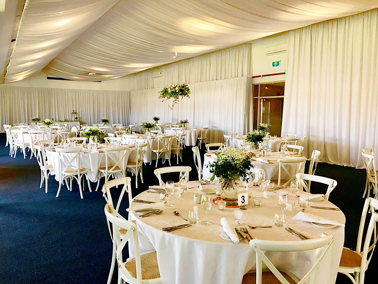 Beautiful wedding dining room setting with white tables and curtains adorning the ceiling, bouquets at the centre of each of the 10 round tables