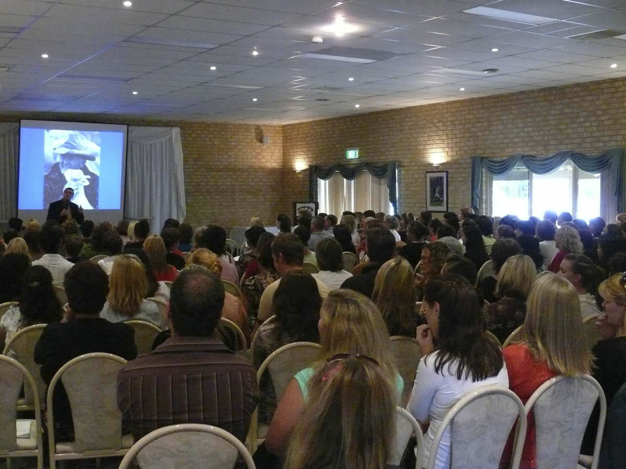 A Speaker Conducting A Conference With Projection Screen
