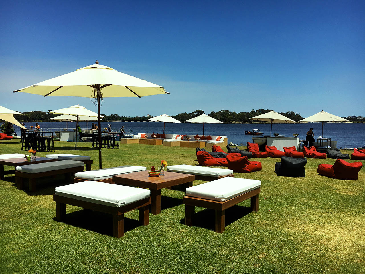 Wooden settees with white cushions underneath sun umbrellas. Swan river and trees fill the back drop