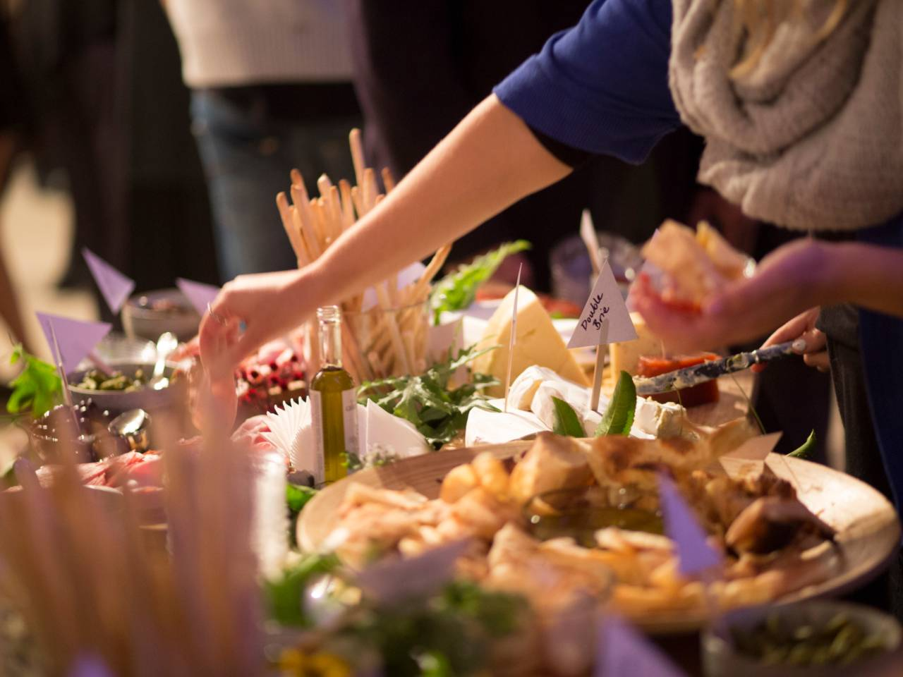Table Of Cocktail Food At A An Event Function With One Of The Guests Reaching To Take Something.