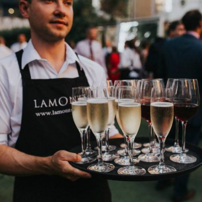 Waiter holding a tray with glasses of champagne at the outdoor event