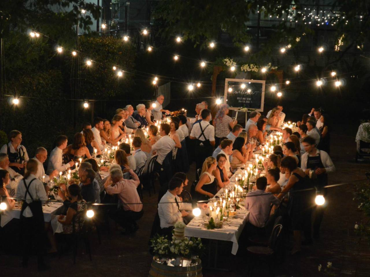 Long tables at night time with festoon lighting and guests sitting, enjoying the private function