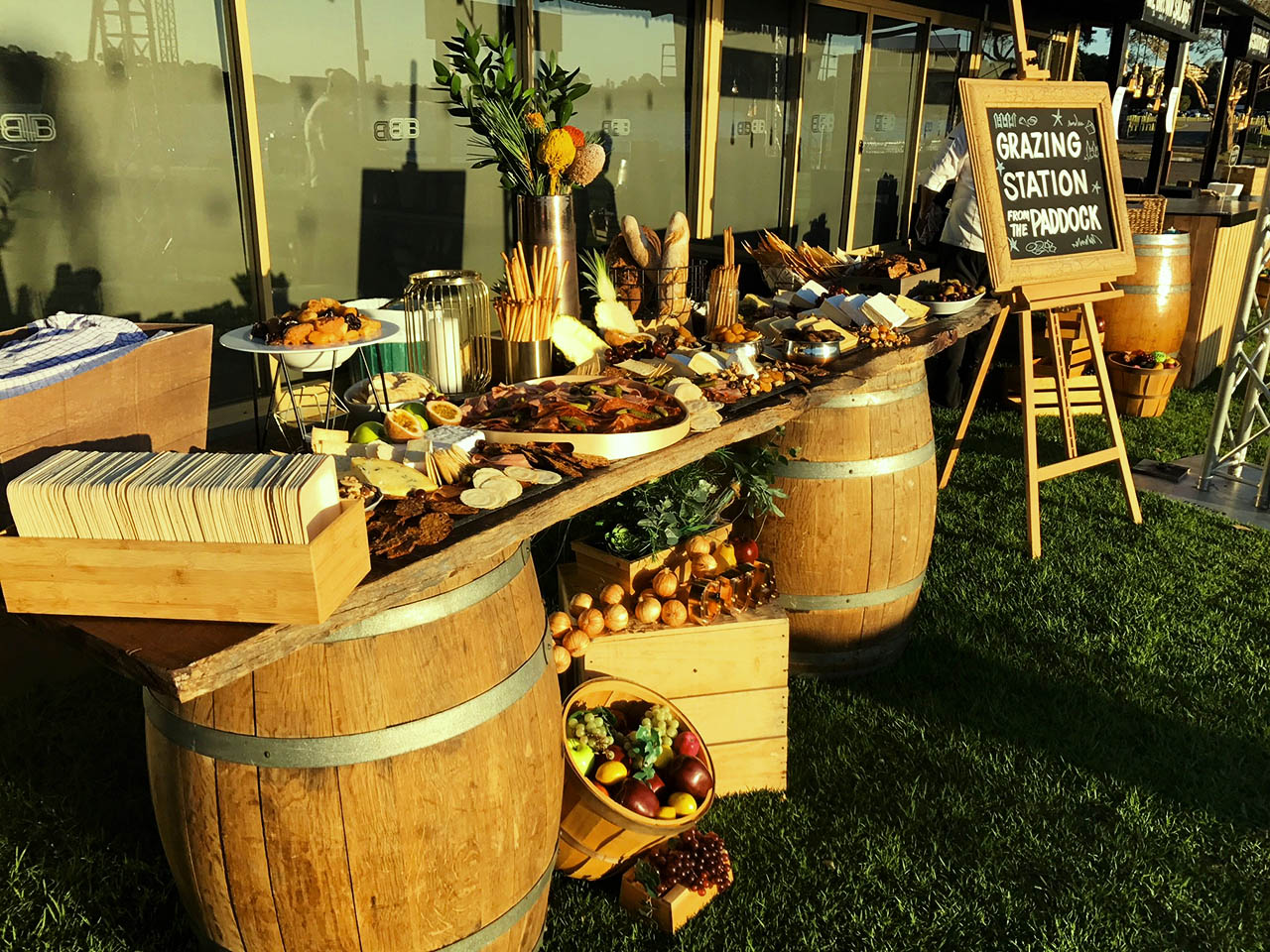 Buffet of canapes and fruit atop wine barrel table
