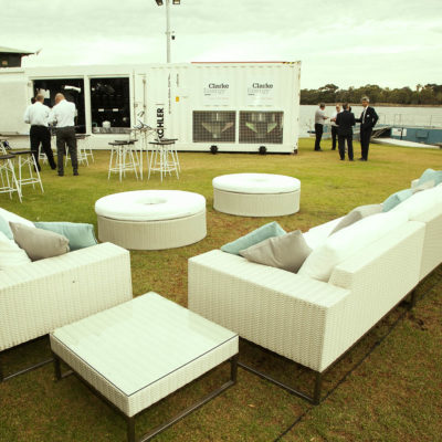 Lawn scene with white settees - square and round- on the riverside with guests mingling in background