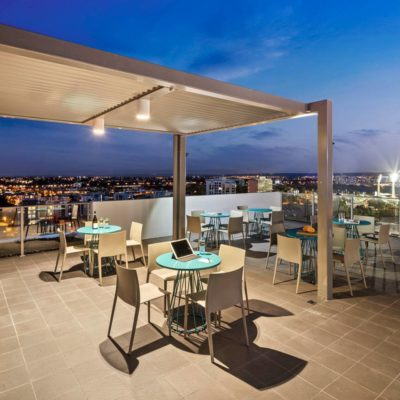 Rooftop Venue Overlooking Perth City Set Up With Tables And Chairs At Night.