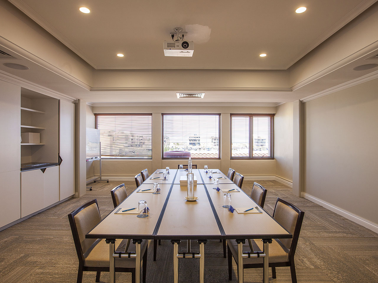 A Meeting Room With Open Windows And A Long Table.
