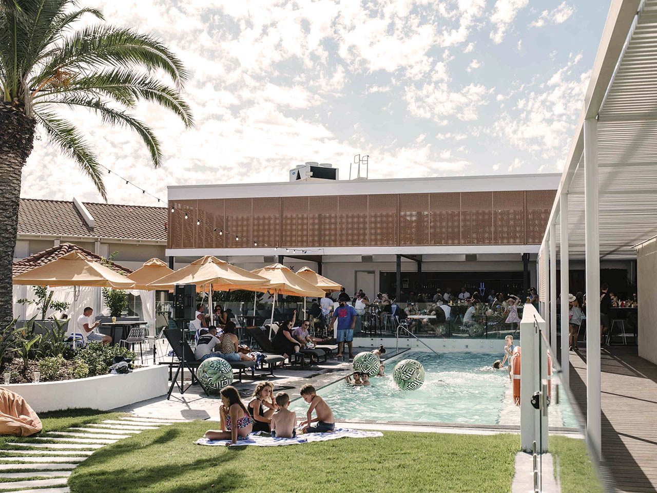 Poolside Scene With Green Grass And People Standing And Sitting In Loungers Enjoying Themselves.