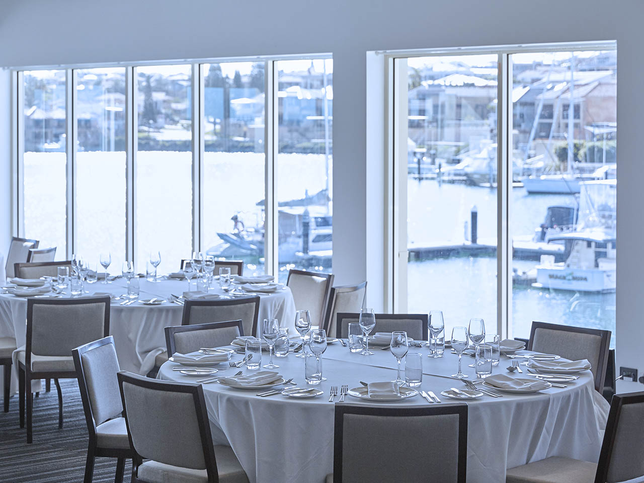 Event Venue With White Chairs, White Table Cloths And Surround Windows Overlooking The Marina.
