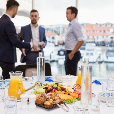 A Networking Event With White Tables, Surround Windows Overlooking The Marina And People Standing Chatting With Each Other. There Is A Foreground Of Fruit Juice, Fruit And Pastries.