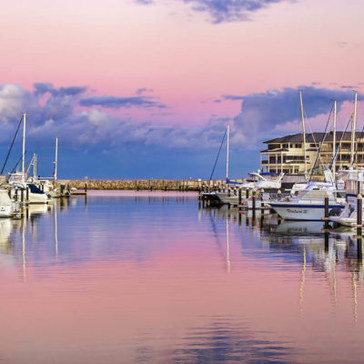 Marina At Sunset With Calm Water And Beautiful Docked Yachts.