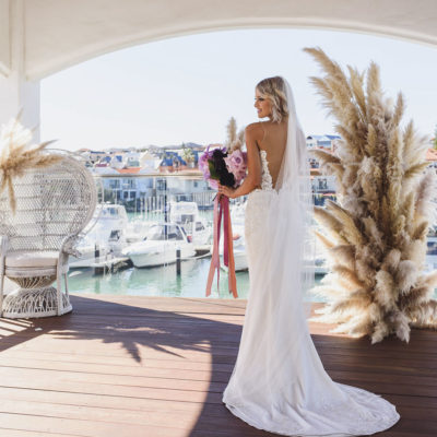 A Beautiful Bride Stood On A Balcony Overviewing Mindarie Marina.