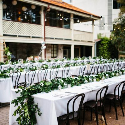 Long tables set up for wedding on lower paved area at Lamont's Bishops House