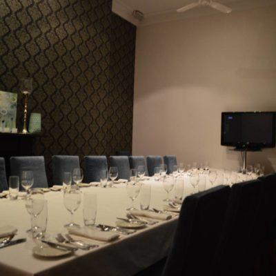 Long table set up with television ready for a dinner boardroom presentation