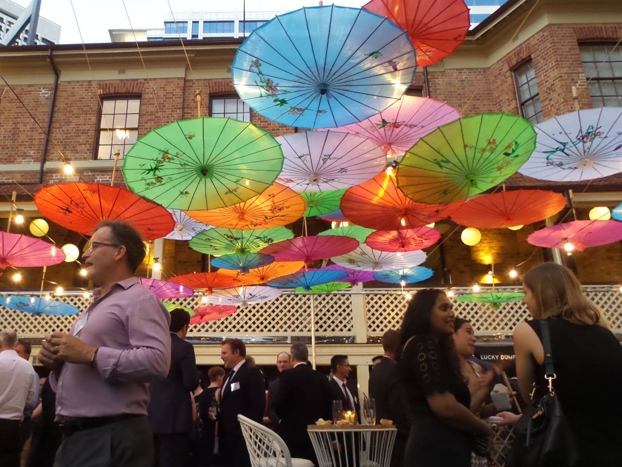 Cocktail event with colourful hanging upside down umbrellas for decoration on lower paved area at Lamont's Bishops House