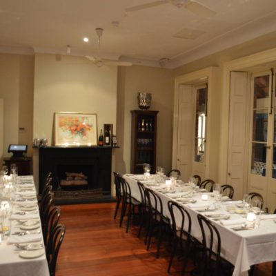 2 long tables set up ready for a meal in a private dining room