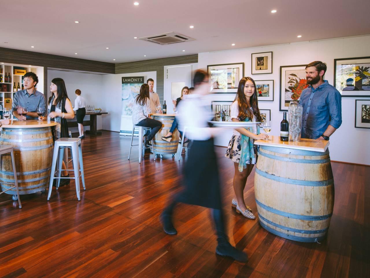 People Mingling In A Private Function Room With Wine Barrels As Tables.
