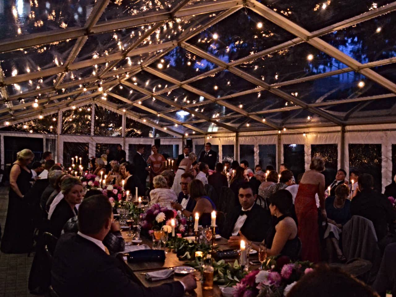 The Marquee With Guests Eating And Talking With Fairylights All Over The Celling.